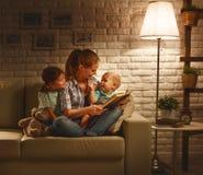Familie vor schlafen gehender Mutter liest Kinderbuch über Lampe stockfotografie