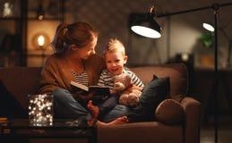 Familie vor schlafen gehender Mutter liest zu ihrem Kindersohnbuch nahe einer Lampe am Abend lizenzfreie stockfotos
