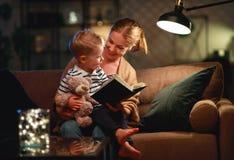 Familie vor schlafen gehender Mutter liest zu ihrem Kindersohnbuch nahe einer Lampe am Abend lizenzfreie stockbilder