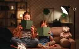 Familie vor schlafen gehender Mutter liest zu ihrem Kindertochterbuch nahe einer Lampe am Abend stockbilder