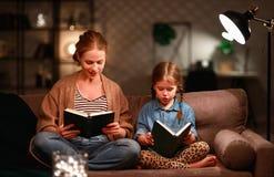 Familie vor schlafen gehender Mutter liest zu ihrem Kindertochterbuch nahe einer Lampe am Abend stockfoto