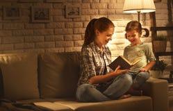 Familie vor schlafen gehender Mutter liest zu ihrer Kindertochter BO lizenzfreie stockfotografie