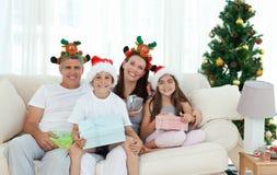Familie während des Weihnachtstages, der die Kamera betrachtet Stockfotos
