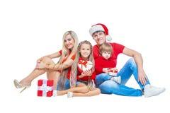 Familie am Weihnachten Nette Familie in Sankt-Hüten, die Kamera betrachten und während Sie auf Weiß lächeln, lokalisiert werden P stockfotos