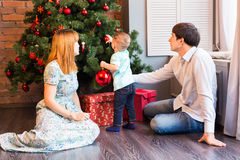 Familie, Weihnachten, Weihnachten, Winter, Glück und Leutekonzept - lächelnde Familie, die Weihnachtsbaum verziert Stockbild