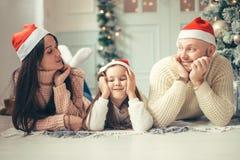 Familie in Weihnachts-Sankt-Hüten, die auf Bett liegen Muttervater und -baby, die Spaß haben lizenzfreies stockbild