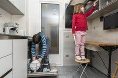 Familie, welche die Spülmaschine leert Lizenzfreie Stockfotos