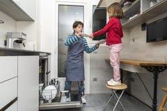 Familie, welche die Spülmaschine leert Stockbilder
