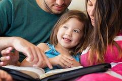 Familie, welche zusammen die Bibel liest Stockbilder