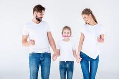 Familie in witte t-shirts die zich en tandenborstels verenigen houden royalty-vrije stock afbeeldingen