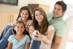 Familie in woonkamer met afstandsbediening stock foto's