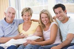 Familie in woonkamer met baby stock afbeelding