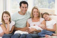 Familie in woonkamer met baby Stock Foto