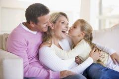 Familie in woonkamer met jonge meisje het kussen woma royalty-vrije stock foto's