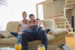 Familie zu Hause unter Verwendung des Tablet-Computers Lizenzfreies Stockfoto