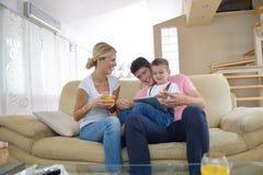Familie zu Hause unter Verwendung des Tablet-Computers Stockbild