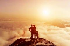Familie zusammen auf dem Berg, der auf Sonnenuntergang cloudscape schaut Lizenzfreie Stockbilder