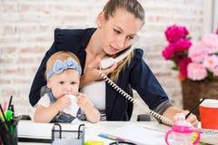 Familiebedrijf - werk Onderneemster tele- en de moeder met jong geitje maakt een telefoongesprek stock foto