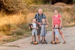 Familiegang op autopedden met zijn vrouw en kinderen op de dorpsweg Stock Afbeelding