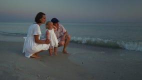 Familiegangen op het Strand Oudersgang met hun kleine dochter langs de kust Ouders naast hun worden gebogen die stock footage
