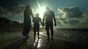 Familiegangen op het Strand Oudersgang met hun zoon langs de kust Zij zijn gelukkig De zon glanst helder stock videobeelden