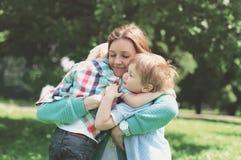 Familiegeluk! Gelukkige moeder die teder zijn twee zonen omhelzen Royalty-vrije Stock Afbeelding