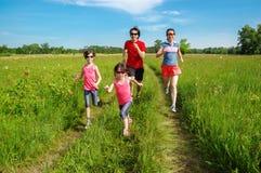 Familiegeschiktheid in openlucht, ouders met jonge geitjes die in park aanstoten, die samen lopen Royalty-vrije Stock Foto