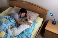 Familiehond en tienermeisje die bed delen tijdens nacht stock foto's