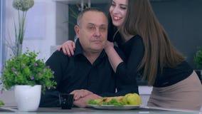 Familieidylle, volwassen dochter en vader die elkaar koesteren close-up op keuken stock video