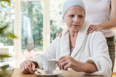 Familielid ondersteunend ziek bejaarde met kanker stock afbeelding