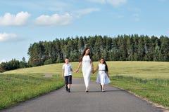Familiemamma en twee kinderenmeisje en jongen die op de weg in het park onder de de tarwegebieden en bossen lopen Royalty-vrije Stock Foto