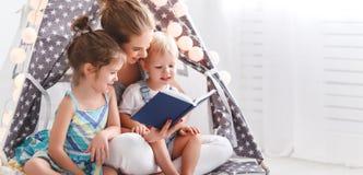 Familiemoeder die aan kinderenboek thuis lezen in tent stock fotografie