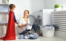 Familiemoeder en kind weinig superherohelper in wasserijruimte Stock Afbeeldingen
