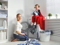 Familiemoeder en kind weinig superherohelper in wasserijruimte Royalty-vrije Stock Afbeelding