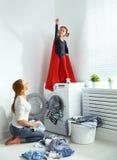 Familiemoeder en kind weinig superherohelper in wasserijruimte Royalty-vrije Stock Foto