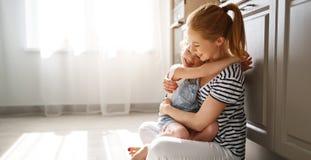 Familiemoeder en kinddochter die in keuken op vloer koesteren royalty-vrije stock afbeelding