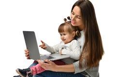 Familiemoeder en kinddochter thuis met laptop stock foto