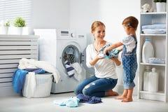 Familiemoeder en kindmeisje in wasserijruimte dichtbij wasmachi stock foto's