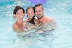Familiemoeder en vader met dochter in het portret van de vakantiepool royalty-vrije stock afbeelding