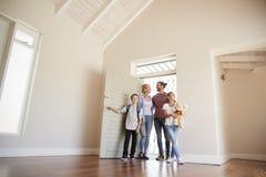 Familien-Öffnungs-Tür und Gehen in leeren Aufenthaltsraum des neuen Hauses stockbild