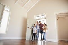 Familien-Öffnungs-Tür und Gehen in leeren Aufenthaltsraum des neuen Hauses stockfoto
