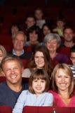 Familien-überwachender Film im Kino stockfotografie