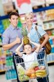 Familien-Antriebswarenkorb mit dem Lebensmittel und kleinem Jungen, die dort sitzen Stockfotografie