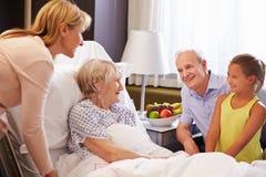 Familien-Besuch zur Großmutter im Krankenhaus-Bett lizenzfreie stockfotos