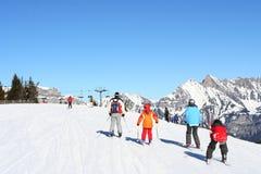 Familien, die in den Alpen Ski fahren lizenzfreie stockbilder