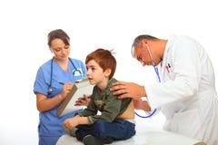 Familien-Doktor mit der Krankenschwester, die einen Jungen überprüft Lizenzfreies Stockbild