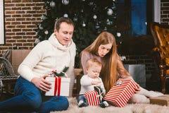 Familien-feierlicher Weihnachtsabend Kaukasische Leute der Familie drei, die unter Koniferenbaum Weihnachtsbaum auf Boden von car lizenzfreies stockfoto