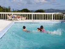Familien-Ferien durch Pool Stockfotografie
