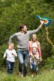 Familien-Fliegen-Drachen in der Landschaft Stockbilder