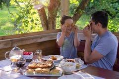 Familien-Frühstück in einem Landhaus Vater und Sohn, die Gesichter mit Pfannkuchen vortäuschen Lizenzfreie Stockfotografie